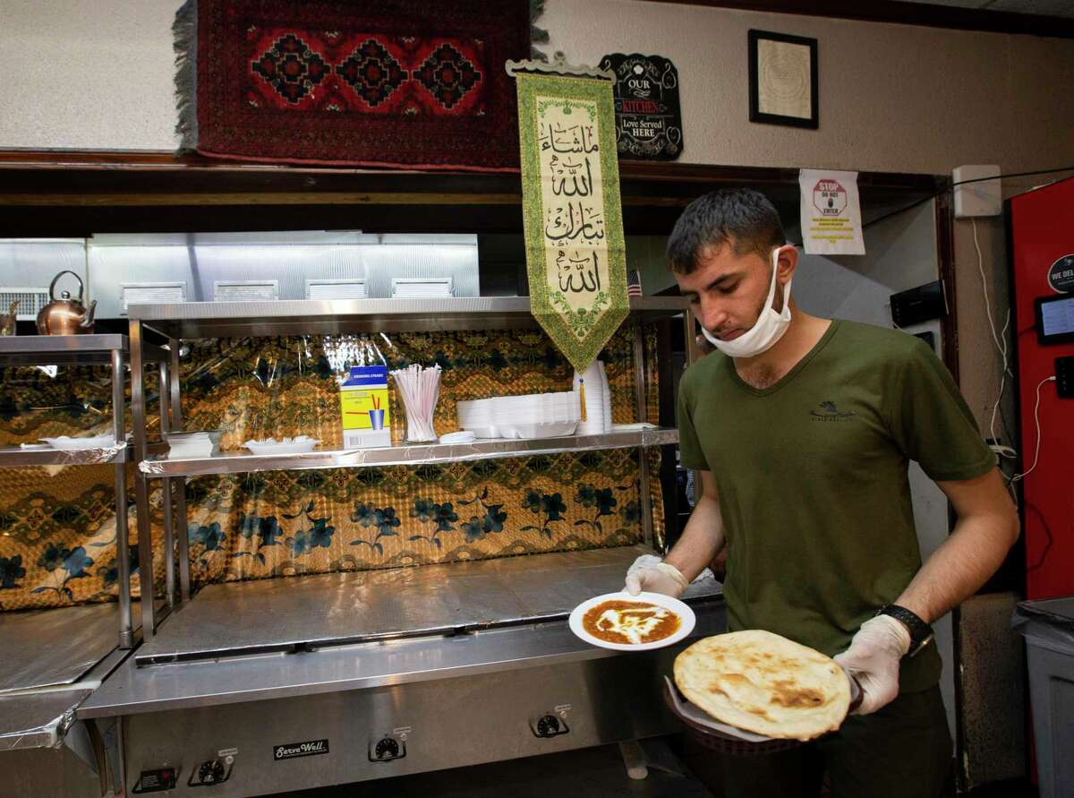 Hazrat Nabi Safi, an employee of the Afghan Village restaurant, brings out dishes to dine-in guests Thursday, Aug. 26, 2021, in Houston. Restaurant Omer Yousafzai came to study law in 2001 before 9/11, and then applied for asylum. He has hired many Afghan Special Immigrant Visa holders like Safi at his business.