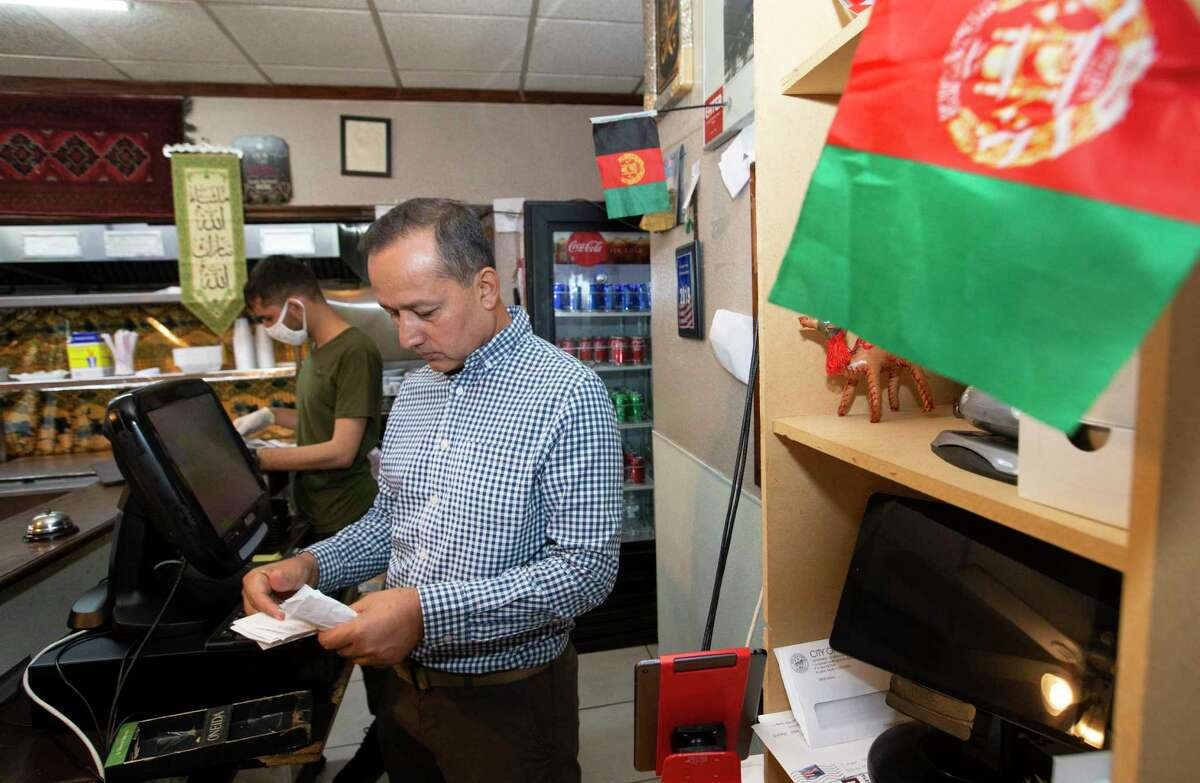 Omer Yousafzai goes through receipts while his employee, Hazrat Nabi Safi, prepares an order for guests at his restaurant, the Afghan Village restaurant, Thursday, Aug. 26, 2021, in Houston. Yousafzai came to study law in 2001 before 9/11, and then applied for asylum. He has hired many Afghan Special Immigrant Visa holder like Safi at his business.