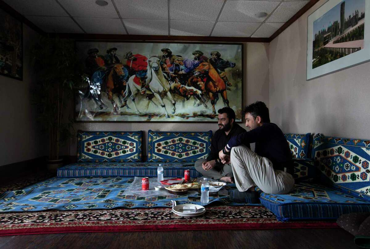 Ezzatullah Hamidi, left, and Dastagir Khan, who both are Afghan Special Immigrant Visa holders, dine at the Afghan Village restaurant on Thursday, Aug. 26, 2021, in Houston. Both men have been living in Austin for a couple of years since coming to the United States. Khan said his wife and children were evacuated from Afghanistan to Qatar several days ago but his daughter fell sick and was in the ICU at a hospital. Therefore, he is trying to apply visa to go to Qatar and see his daughter as soon as he can.