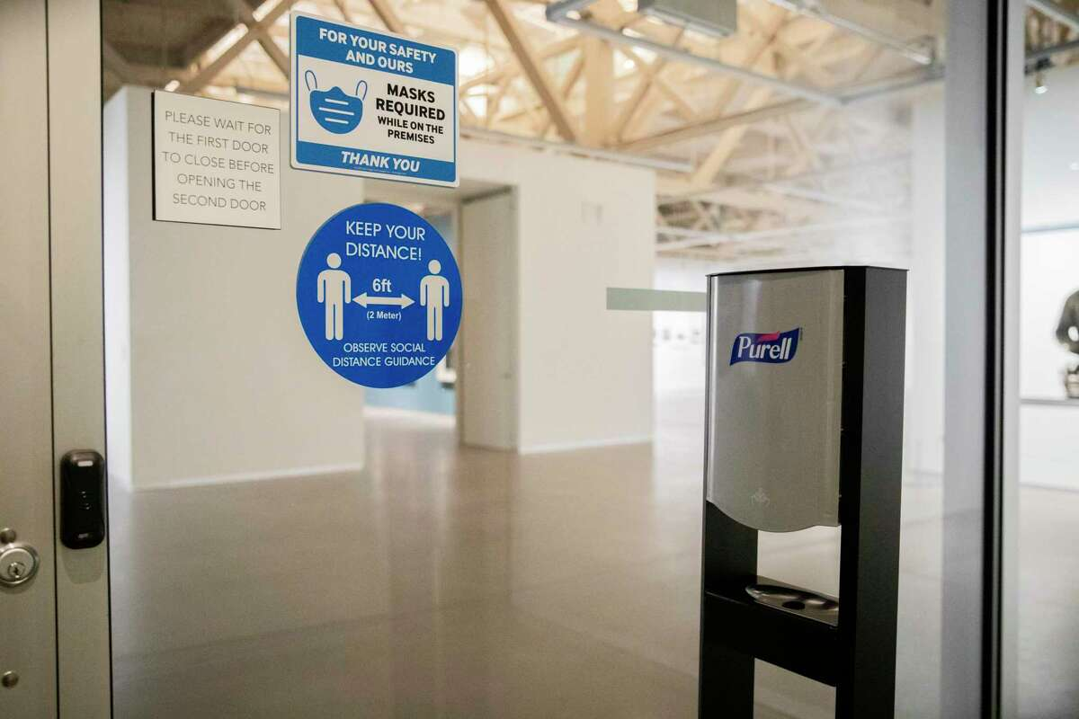 Safety signs and hand sanitizer are seen at Pier 24 Photography in San Francisco in July.