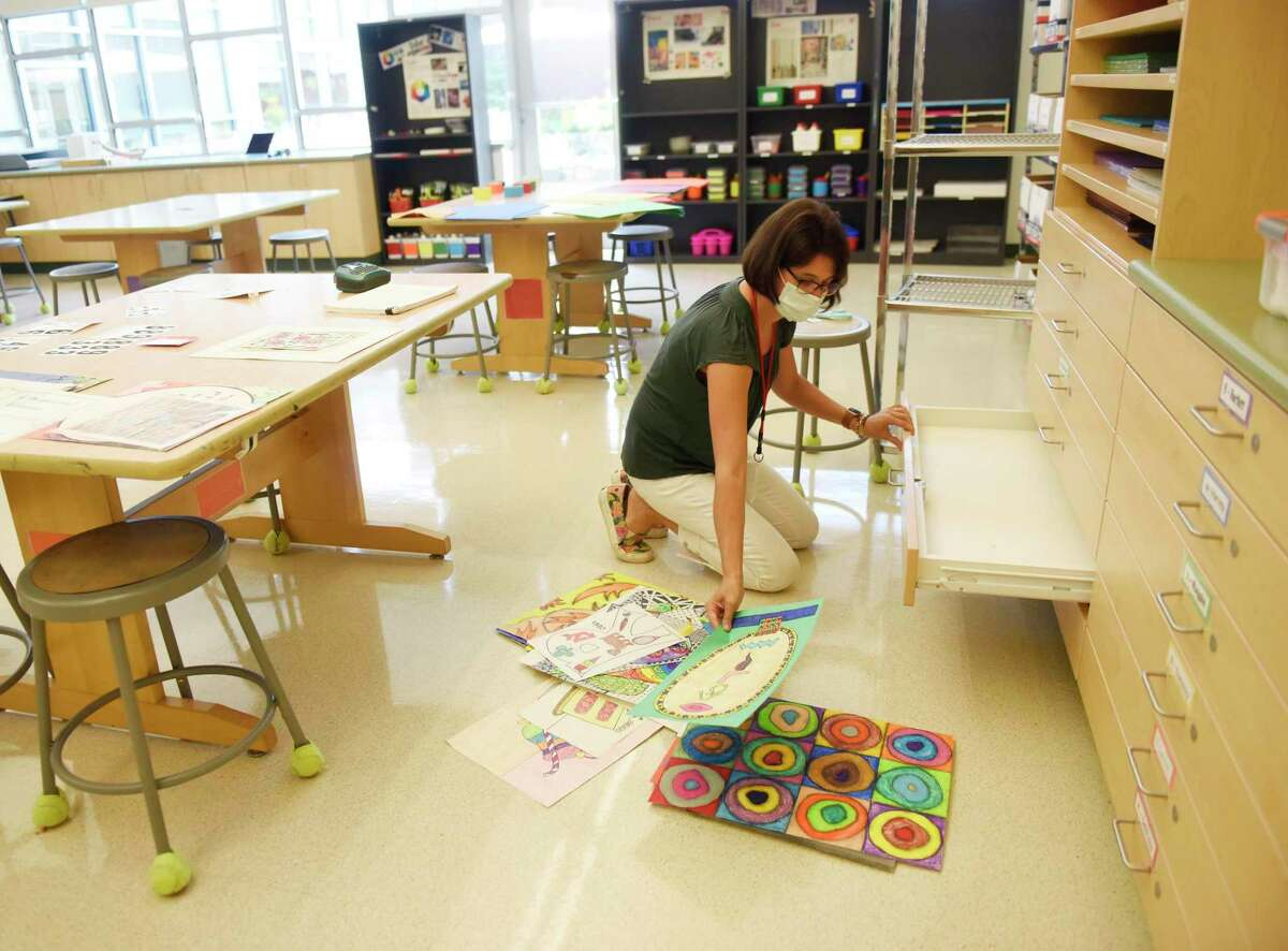 Art teacher Robin Hurta prepares her classroom on the first day back for teachers at Glenville School in the Glenville section of Greenwich, Conn. Thursday, Aug. 26, 2021. Teachers returned to their classrooms Thursday to prepare for the upcoming school year, which begins Wednesday, Sept. 1.
