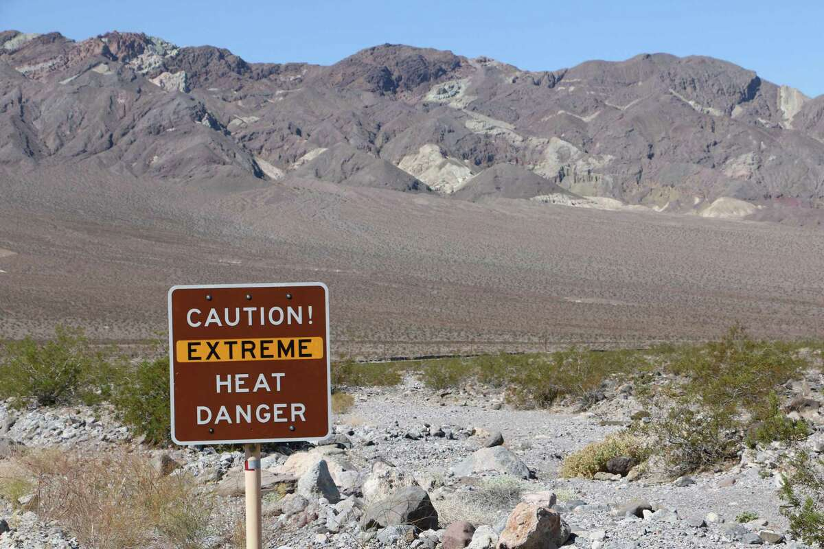 A roadside sign warns visitors as they enter Death Valley National Park about extreme heat. Three hikers have died at the park this summer.