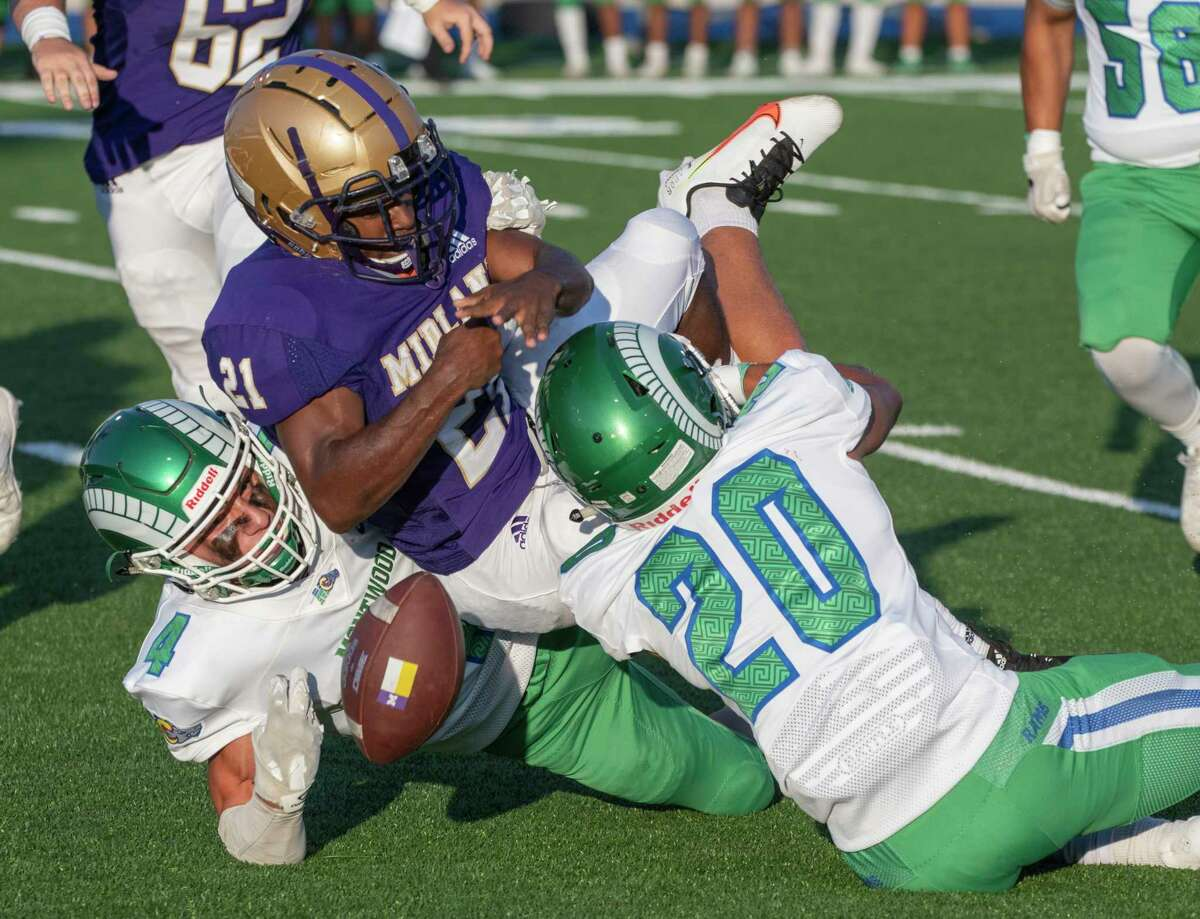 Midland High's Zion Ward has the ball stripped from his arms by El Paso Montwood's Diego Oaxaca, 4, as he is hit by Cameron Harrelson, 20, 08/27/2021 at Grande Communications Stadium. Tim Fischer/Reporter-Telegram