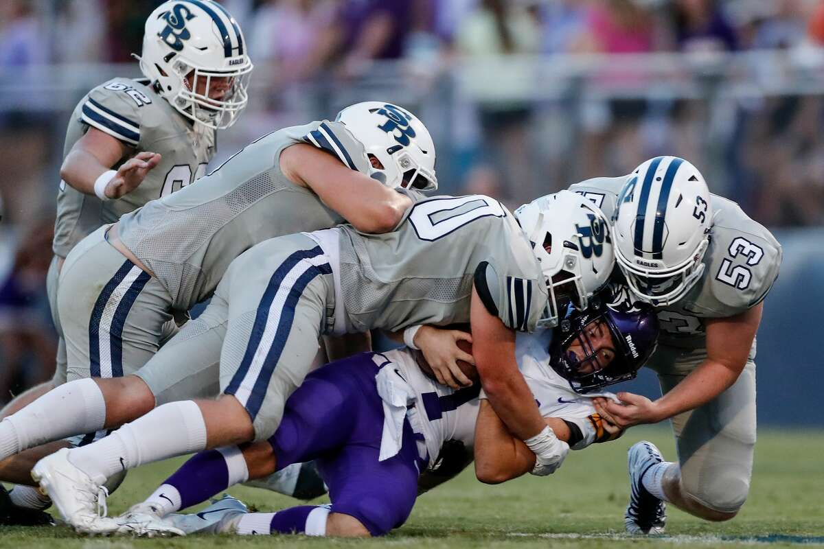 Kinkaid Falcons quarterback Louis Gustafson (1) is sacked by Second Baptist Eagles Reid Cordell (53) and John Dearing (70) during the first half of the high school football game between the Kinkaid Falcons and the Second Baptist Eagles at Eagle Stadium in Houston, TX on Friday, August 27, 2021.
