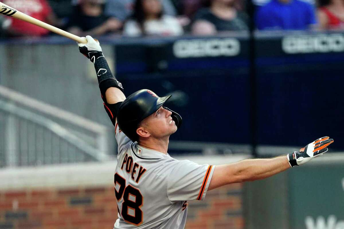 San Francisco Giants' Buster Posey watches his two-run home run during the first inning of the team's baseball game against the Atlanta Braves on Friday, Aug. 27, 2021, in Atlanta. (AP Photo/John Bazemore)