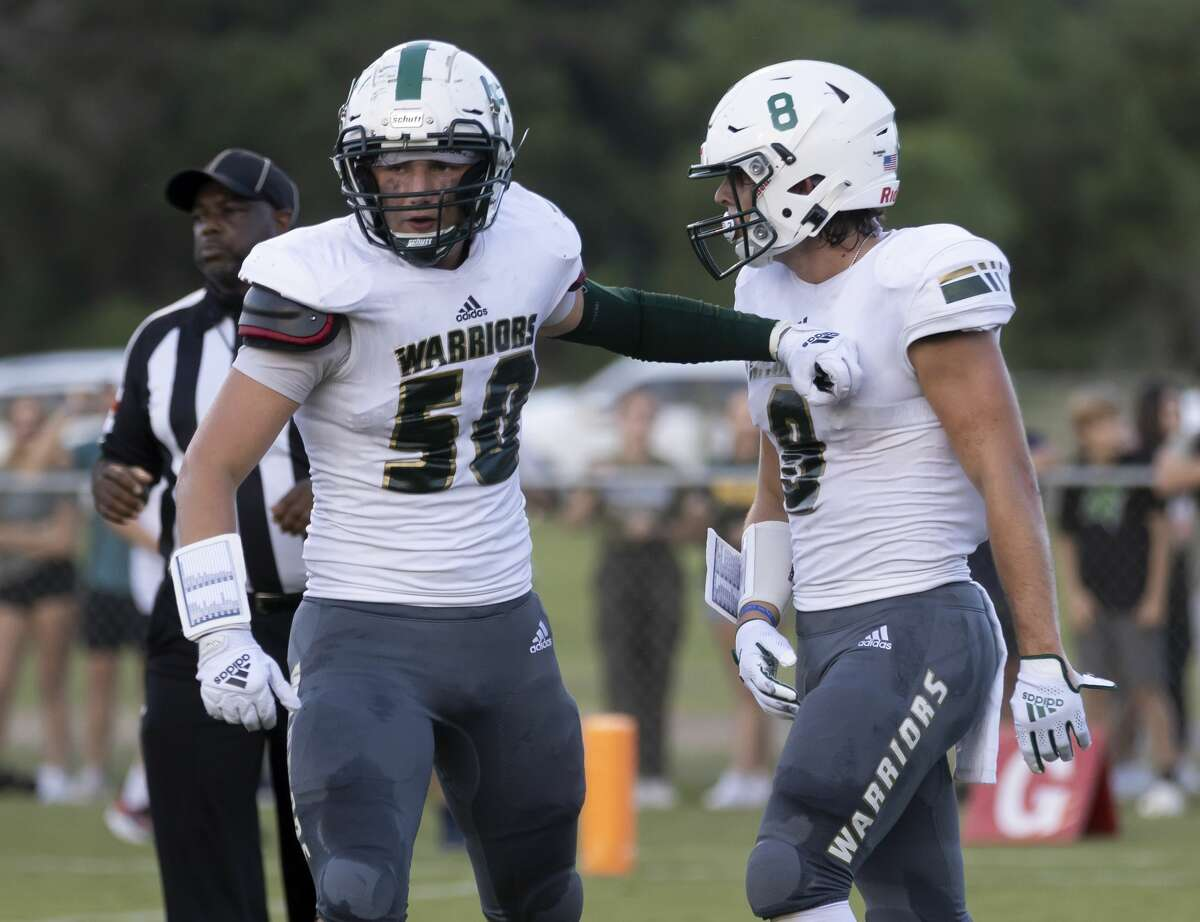 The Woodlands Christian Academy offensive lineman Conner Barham (50) bumps wide receiver Dane Lemaster's chest after Lemaster scores a touchdown during the first quarter of a non-district football game against Legacy Prep Christian Academy at Holcomb Family Field, Friday, Aug. 27, 2021, in Magnolia.