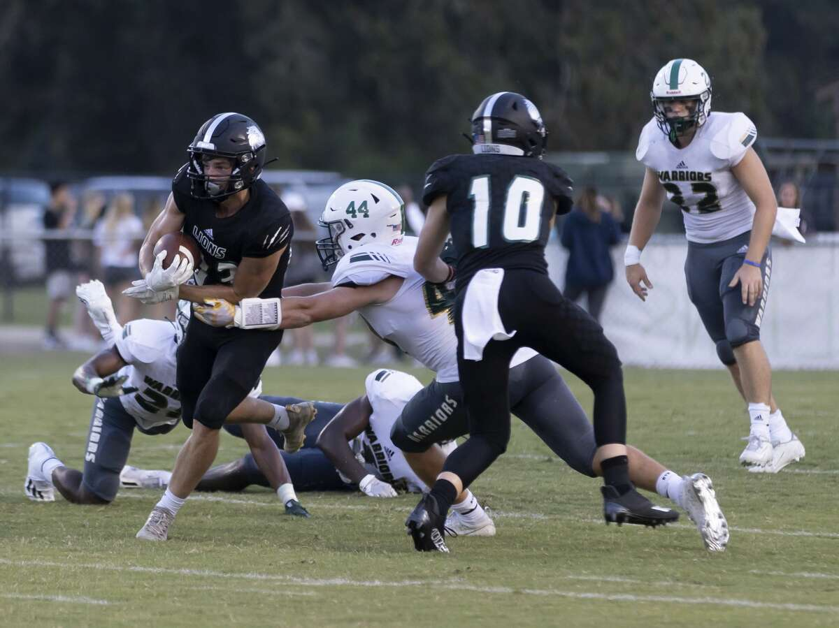 Legacy Prep Christian Academy's Elias Loughmiller (83) runs the ball while under pressure from The Woodlands Christian Academy lineman Jack Van Til (44) during the first quarter of a non-district football game at Holcomb Family Field, Friday, Aug. 27, 2021, in Magnolia.