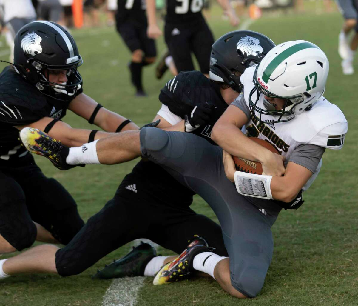 The Woodlands Christian Academy quarterback Josh Johnson (17) is brought down by Legacy Prep Christian Academy's defense during the first quarter of a non-district football game at Holcomb Family Field, Friday, Aug. 27, 2021, in Magnolia.