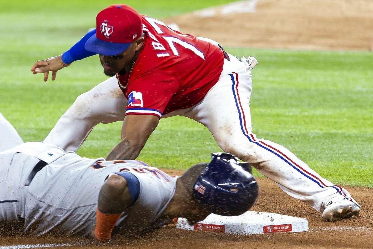 Houston Astros' Martin Maldonado, bottom, slides into third base under a tag byf Texas Rangers third baseman Andy Ibanez (77) during the seventh inning of a baseball game, Friday, Aug. 27, 2021, in Arlington, Texas. (AP Photo/Sam Hodde)