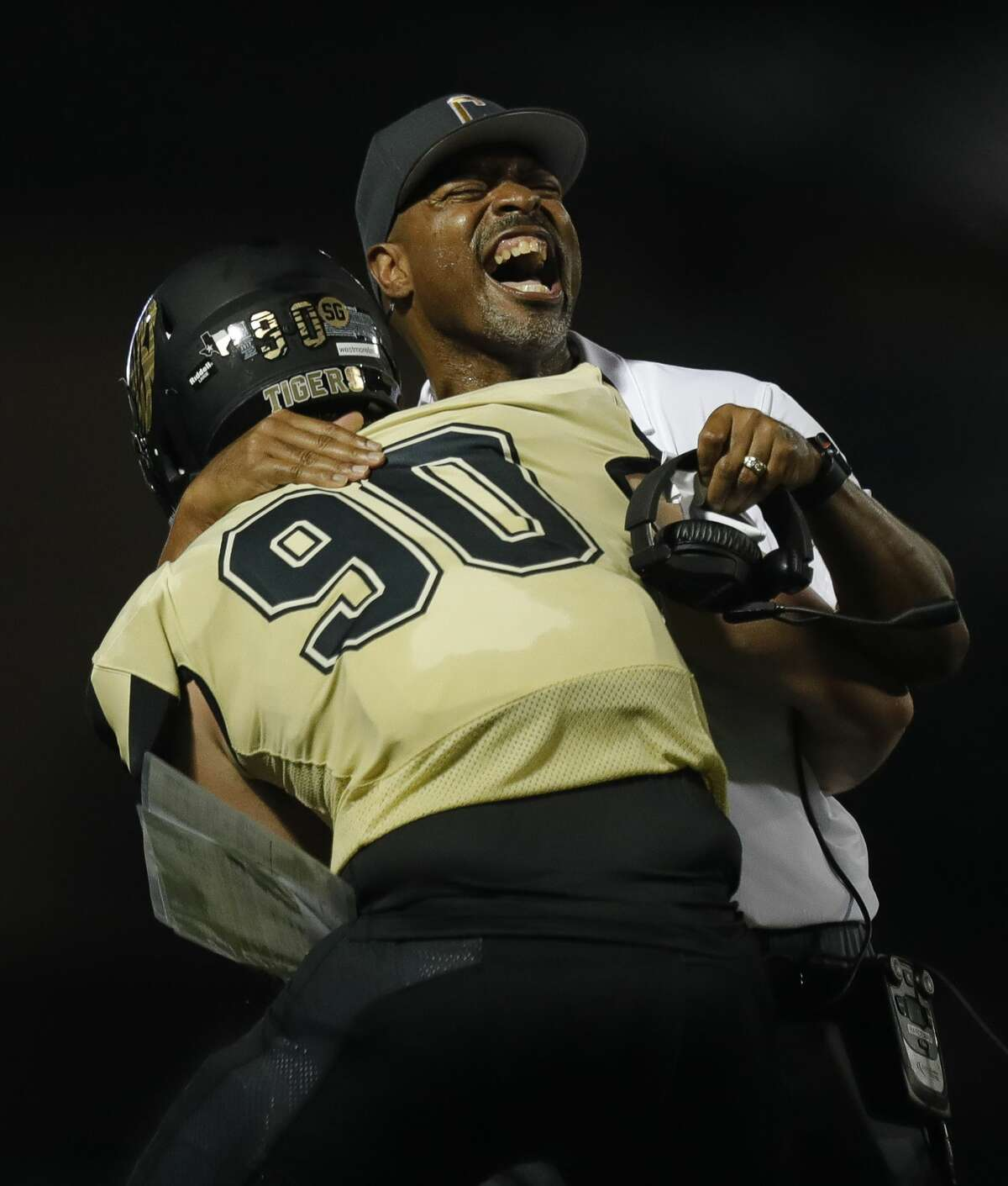 Conroe head coach Cedric Hardeman embraces defensive lineman Matthew Westmoreland (90) after he returned an interception for a 45-yard touchdown during the third quarter of a non-district high school football game at Buddy Moorhead Stadium, Friday, Aug. 27, 2021, in Conroe.