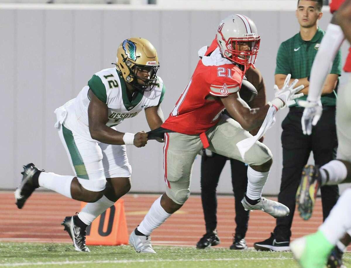 Judson's Devon Boyd-Smith (21) evades a stop by DeSoto quarterback Matt Allen (12) to score a touchdown for the Rockets on Boyd-Smith's interception at Rutledge Stadium on Friday, Aug. 27, 2021.