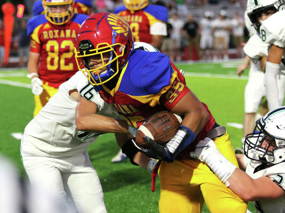 Roxana running back Terrel Graves (middle) powers through a couple Eureka defenders on Friday night at Raich Field.