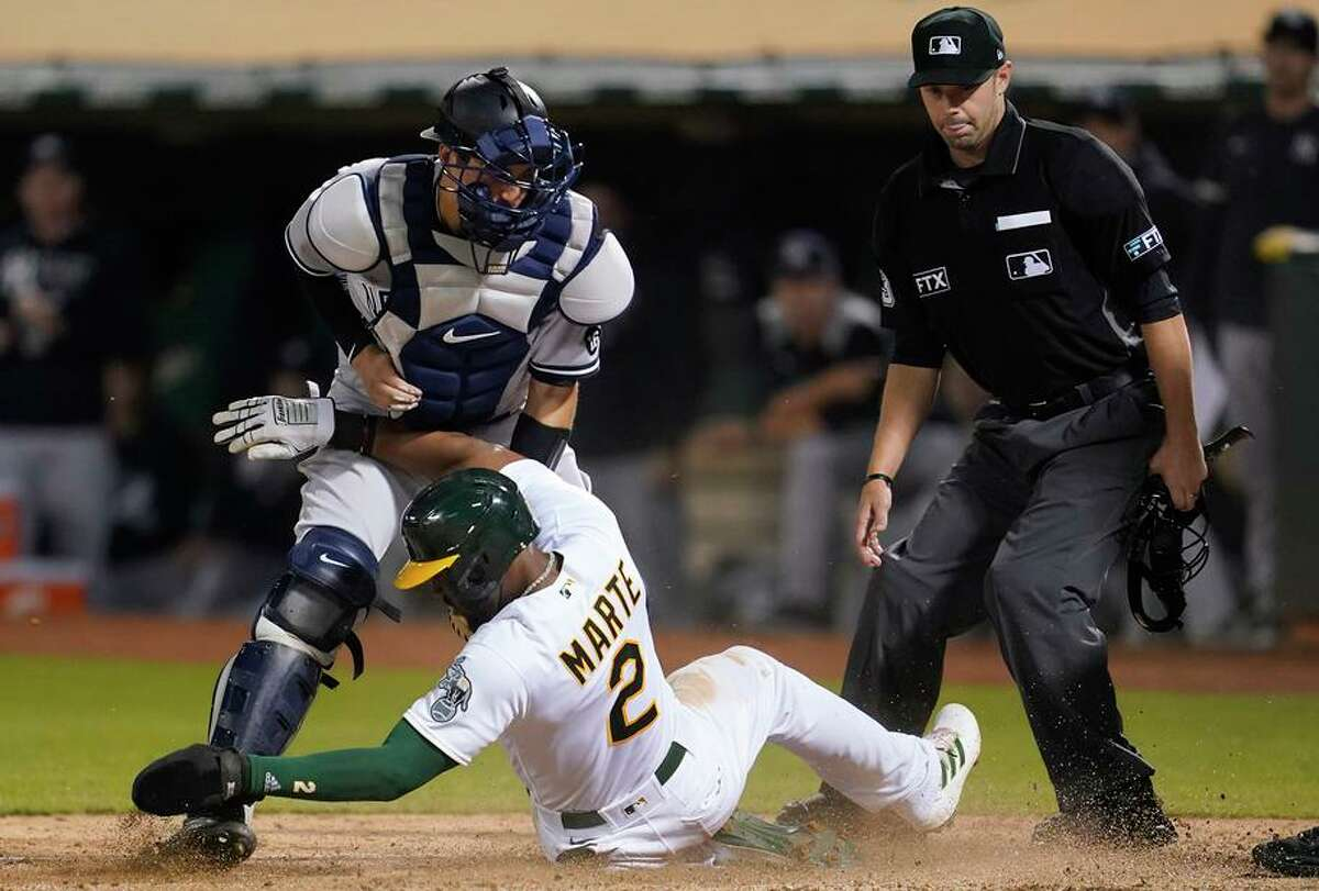 The A's Starling Marte scores next to New York Yankees catcher Kyle Higashioka during the seventh inning of a baseball game in Oakland, Calif., Friday, Aug. 27, 2021. (AP Photo/Jeff Chiu)