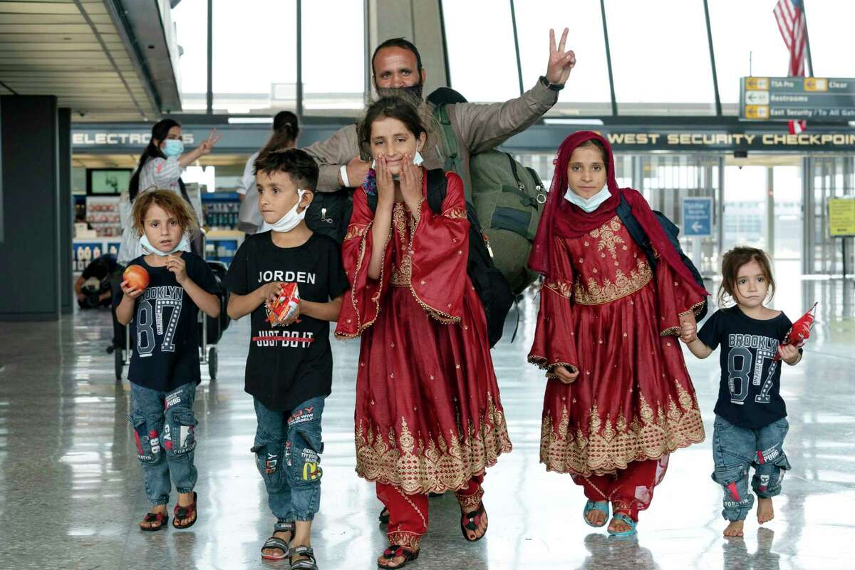 Families evacuated from Kabul, Afghanistan, walk through the terminal before boarding a bus after arriving at Washington Dulles International Airport, in Chantilly, Va., Friday.