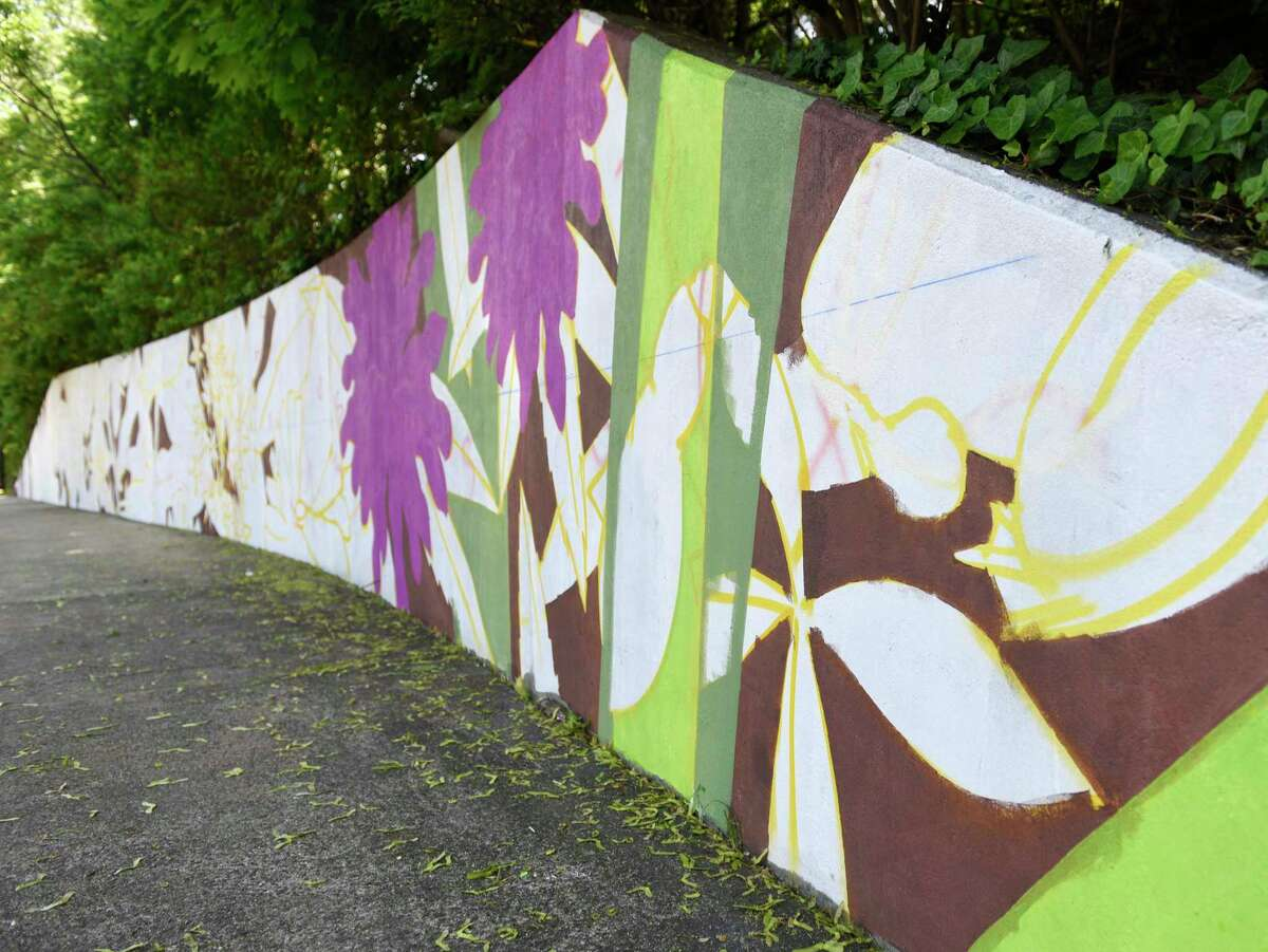 A mural is partially completed on the concrete wall near the bus stop on East Putnam Avenue by Greenwich High School in Greenwich, Conn. Tuesday, May 25, 2021.