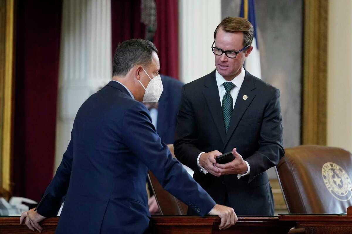 Texas State Rep. Rafael Anchia, D-Dallas, left, talks with Speaker of the House Dade Phelan, R-Orange, right, as they House prepares to debate voting bill SB1, Thursday, Aug. 26, 2021, in Austin, Texas.