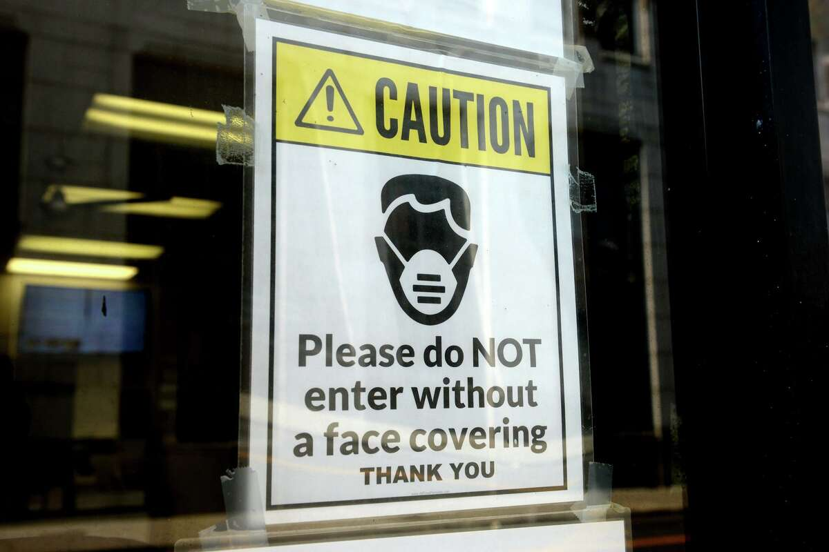 A sign requiring masks or face covering hangs on the front door of the Morton Government Center, in Bridgeport, Conn. Aug. 11, 2021.