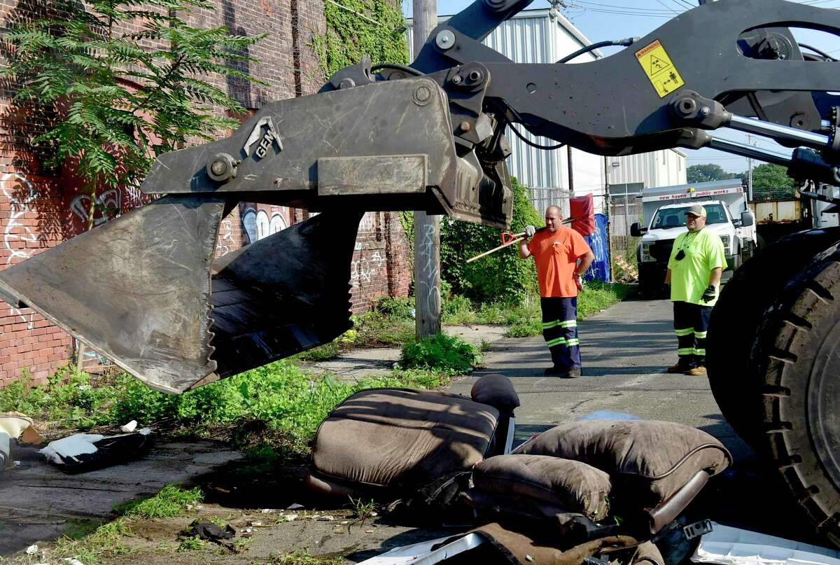 New Haven Public Works Department employees Scott Murphy, left, and Chris Santiago wait to clean up the remains after a payloader picks up a couch and other debris at a frequent and popular dumping site on Wallace Street in Fair Haven Aug. 25, 2021.