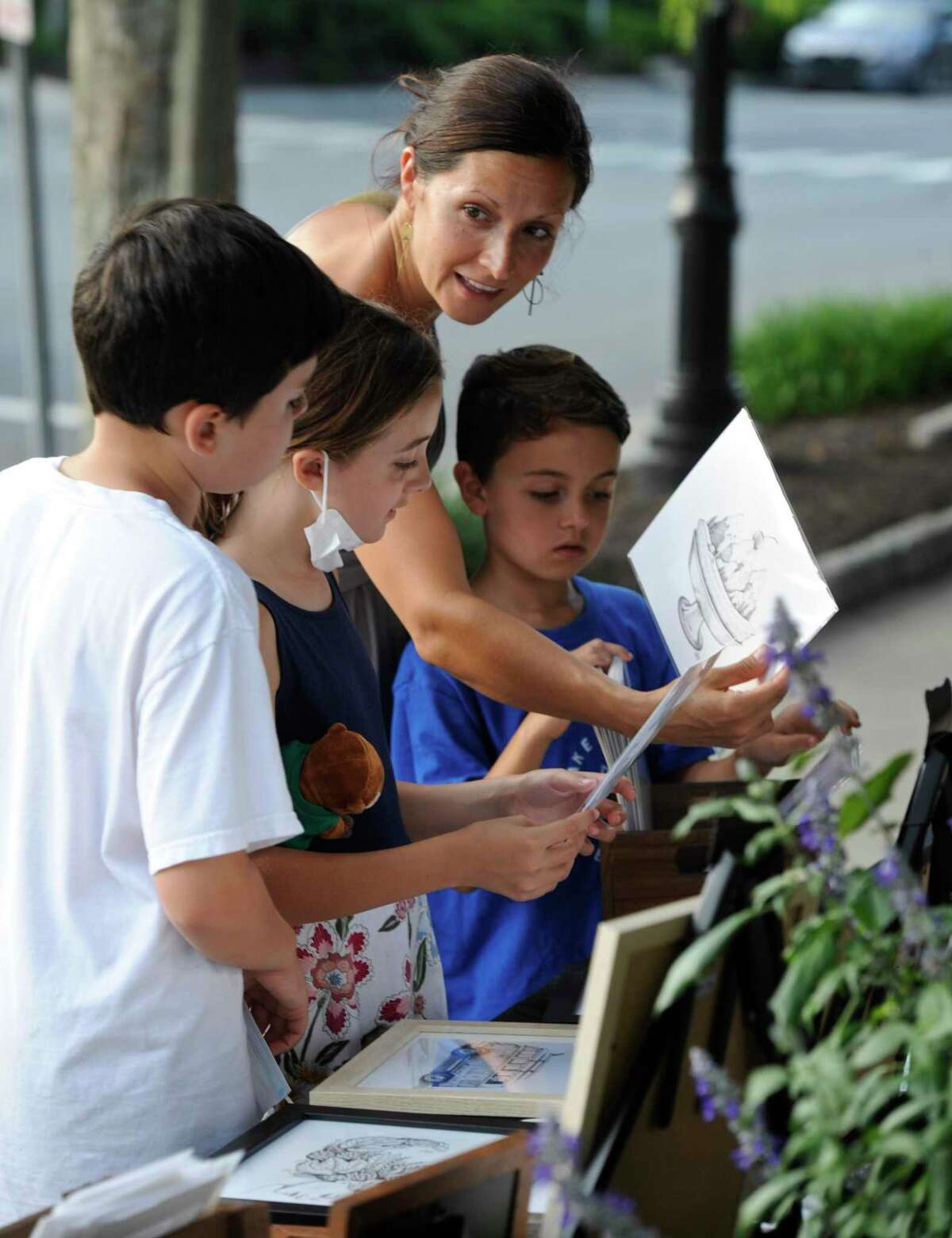 Cassidy Bluhm, of Ridgefield, looks at work by artist Steve Habersang with her children, Aiden, left, age 12, Amelie, age 10 and Emery, age, 7, at the Ridgefield Guild of Artists eighth annual Art Walk, Friday, August 27, 2021, in Ridgefield, Conn.