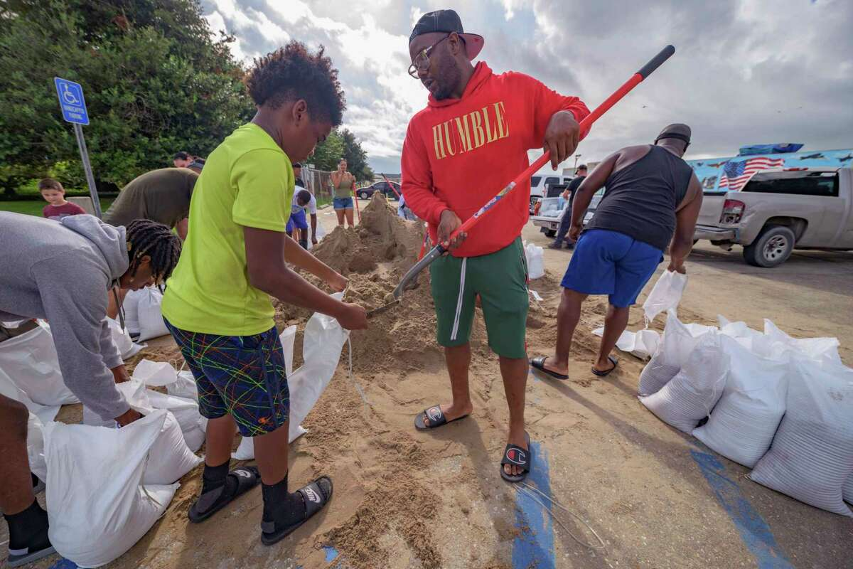Jawan Williams shovels sand for a sandbag held by his son Jayden Williams, before landfall of Hurricane Ida at the Frederick Sigur Civic Center in Chalmette, La., which is part of the Greater New Orleans metropolitan area, Saturday, Aug. 28, 2021. The storm is expected to bring winds as high as 140 mph when it slams ashore late Sunday.