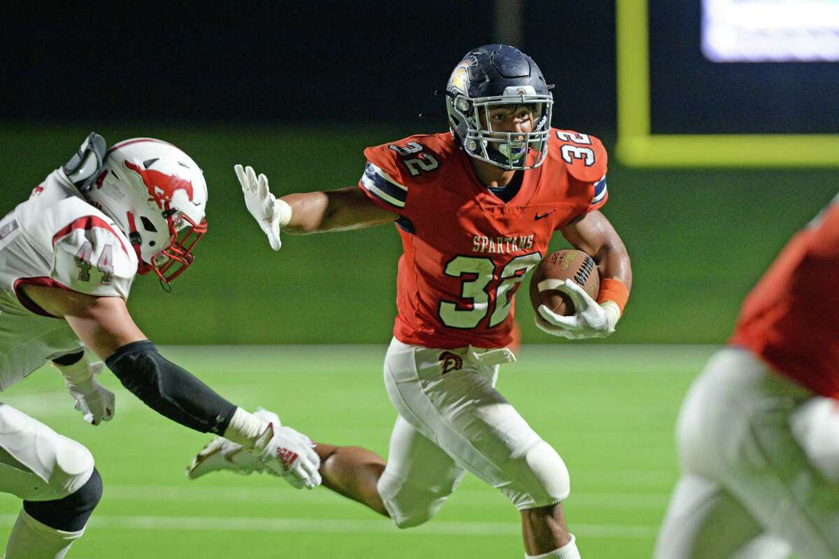 Michael Amico (32) of Seven Lakes runs past Grayson Lincecum (44) of Memorial during the fourth quarter of a non-District football game between the Seven Lakes Spartans and the Memorial Mustangs on Friday, August 27, 2021 at Rhodes Stadium, Katy, TX.