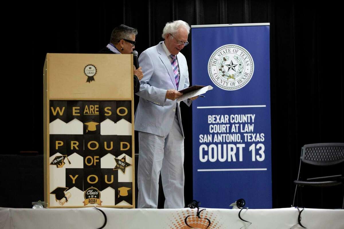 Judge Rosie Speedlin-Gonzalez gives a Semilla award to former county court-at-law judge Al Alonso at the first graduation ceremony of Reflejo Court, a program that helps those charged with misdemeanor domestic violence.