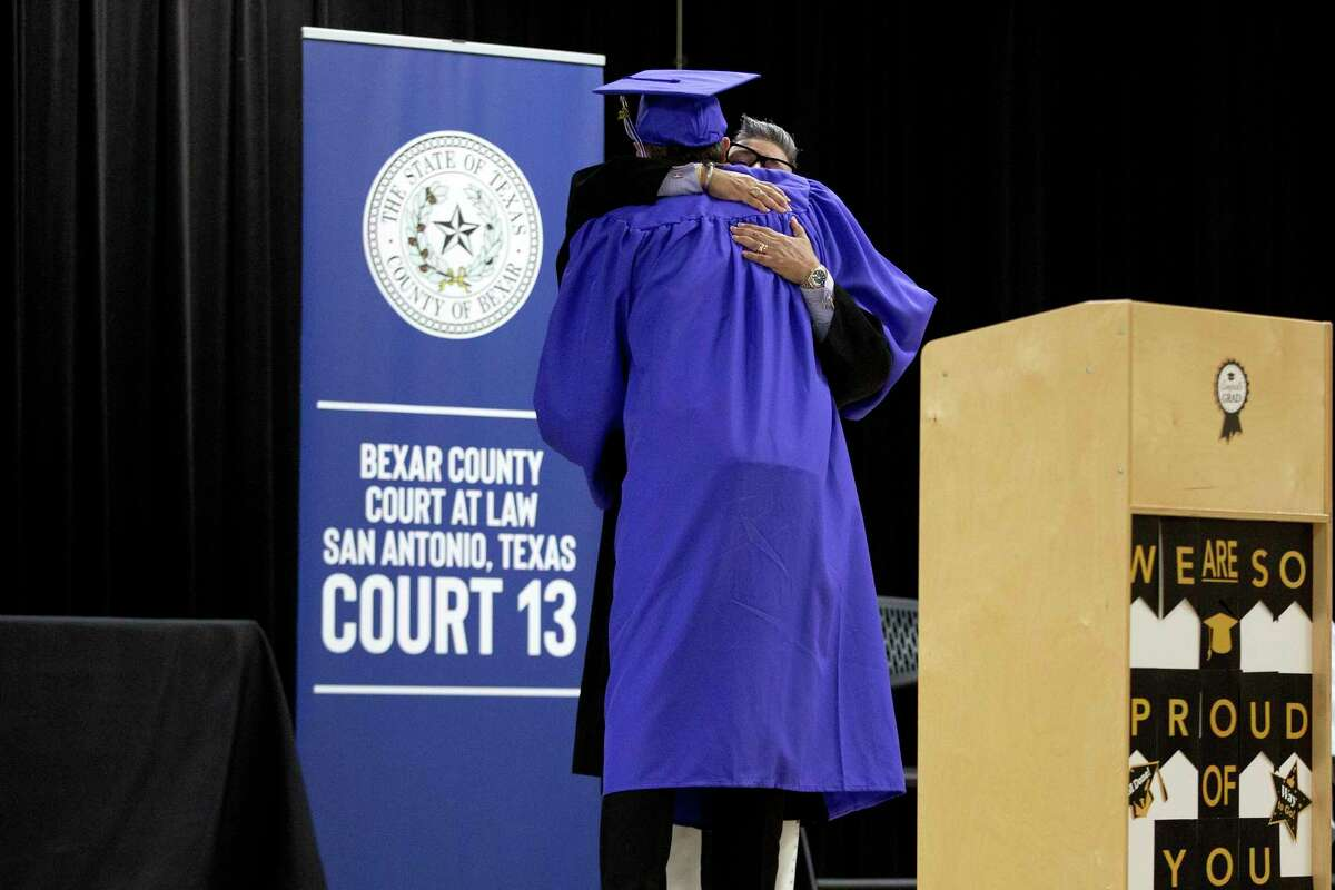 Judge Rosie Speedlin-Gonzalez hugs Patrick K after he graduated from Reflejo, which gives a second chance to adults charged with misdemeanor domestic violence. Participants plead guilty and agree to a year of close supervision.