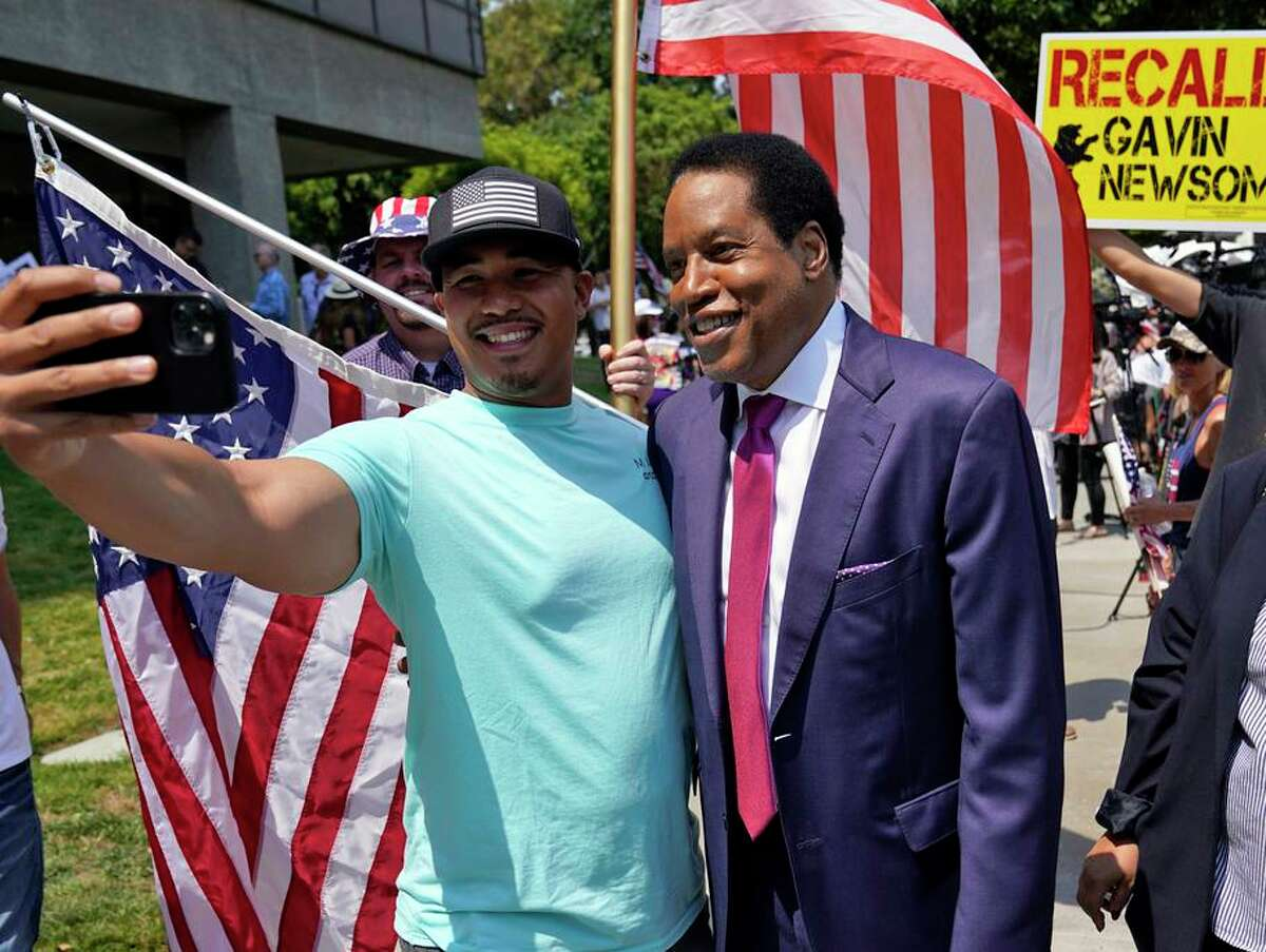 Radio talk show host Larry Elder (right) poses for selfies with supporters during a July campaign stop in Norwalk (Los Angeles County). Elder suggested in a 2010 column that undocumented immigrants should be denied public benefits including education and emergency medical treatment.