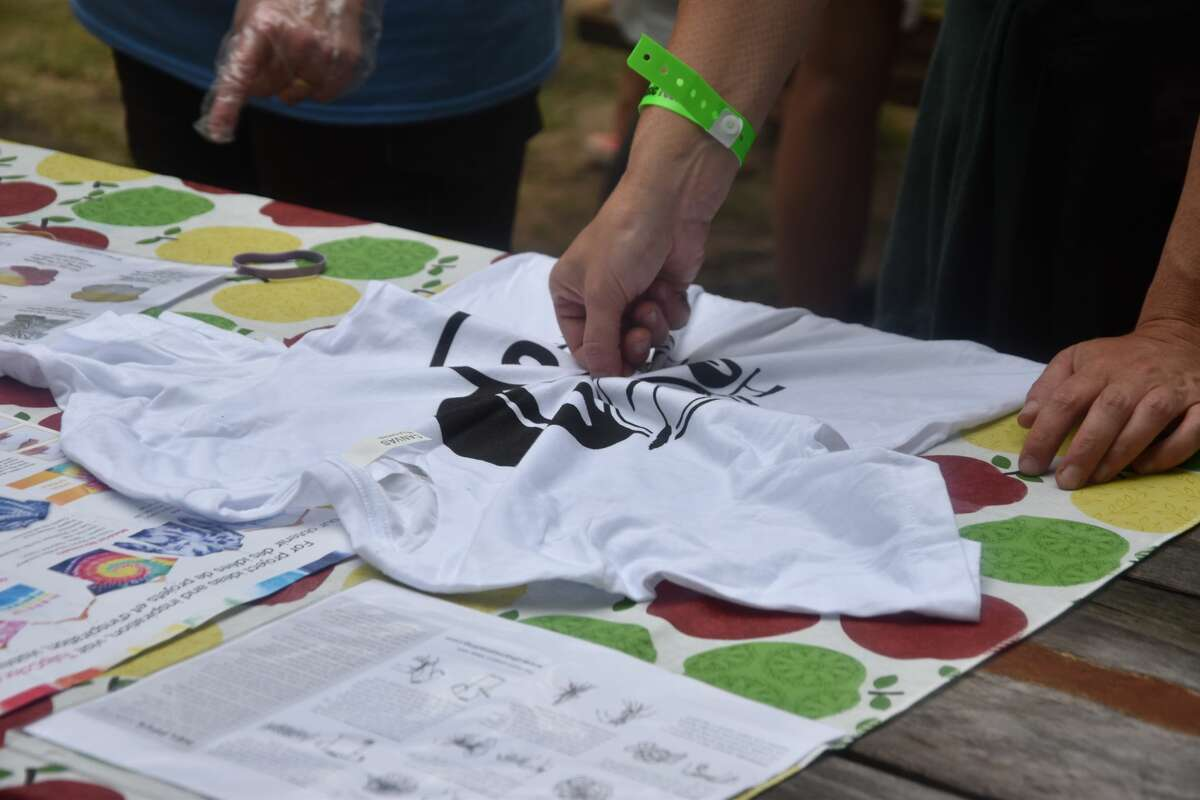 A group was gathered around the tie-dye tables as Forest Trail Music Festival attendees worked with Jen Cameron on tie-dying all manner of clothing on Saturday morning.