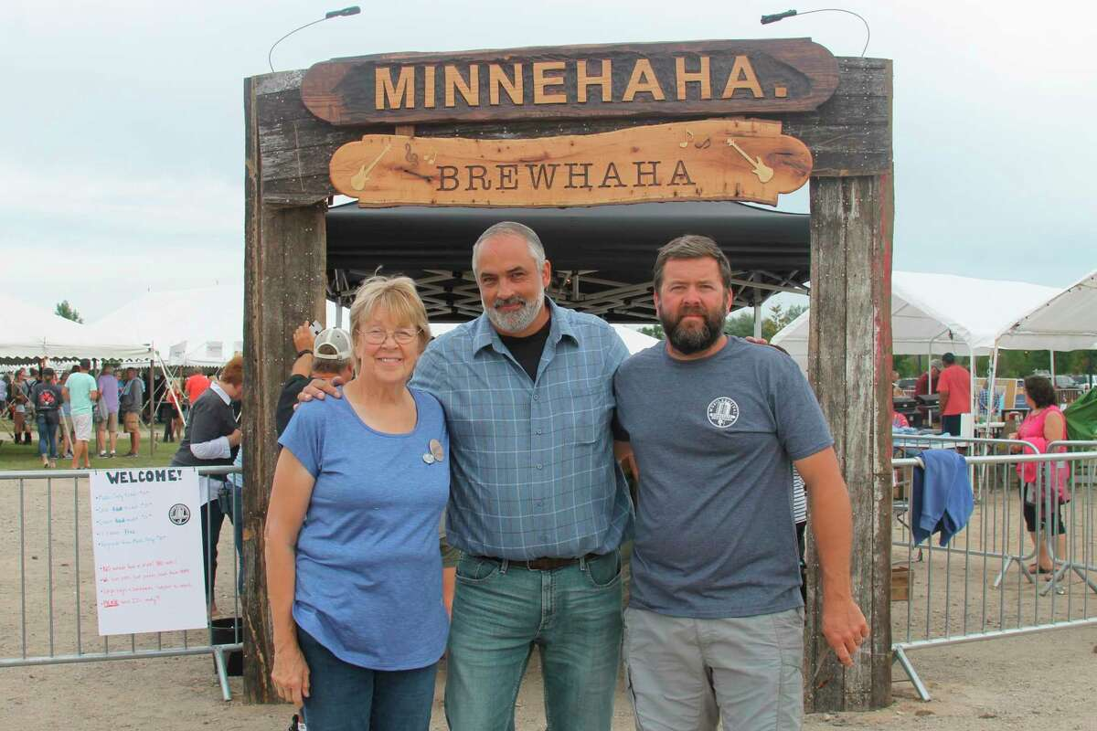 """(From left) Sue Stoops, Kevin Dykstra and Jim Stoops stand at the entrance to the Minnehaha Brewhaha music festivalin 2019. Dykstra, of the History Channel's """"The Curse of the Civil War Gold,"""" is a long-time friend of the Stoops family.The festival was started as a fundraiser for the Ron Stoops Memorial Scholarship program. (File photo)"""