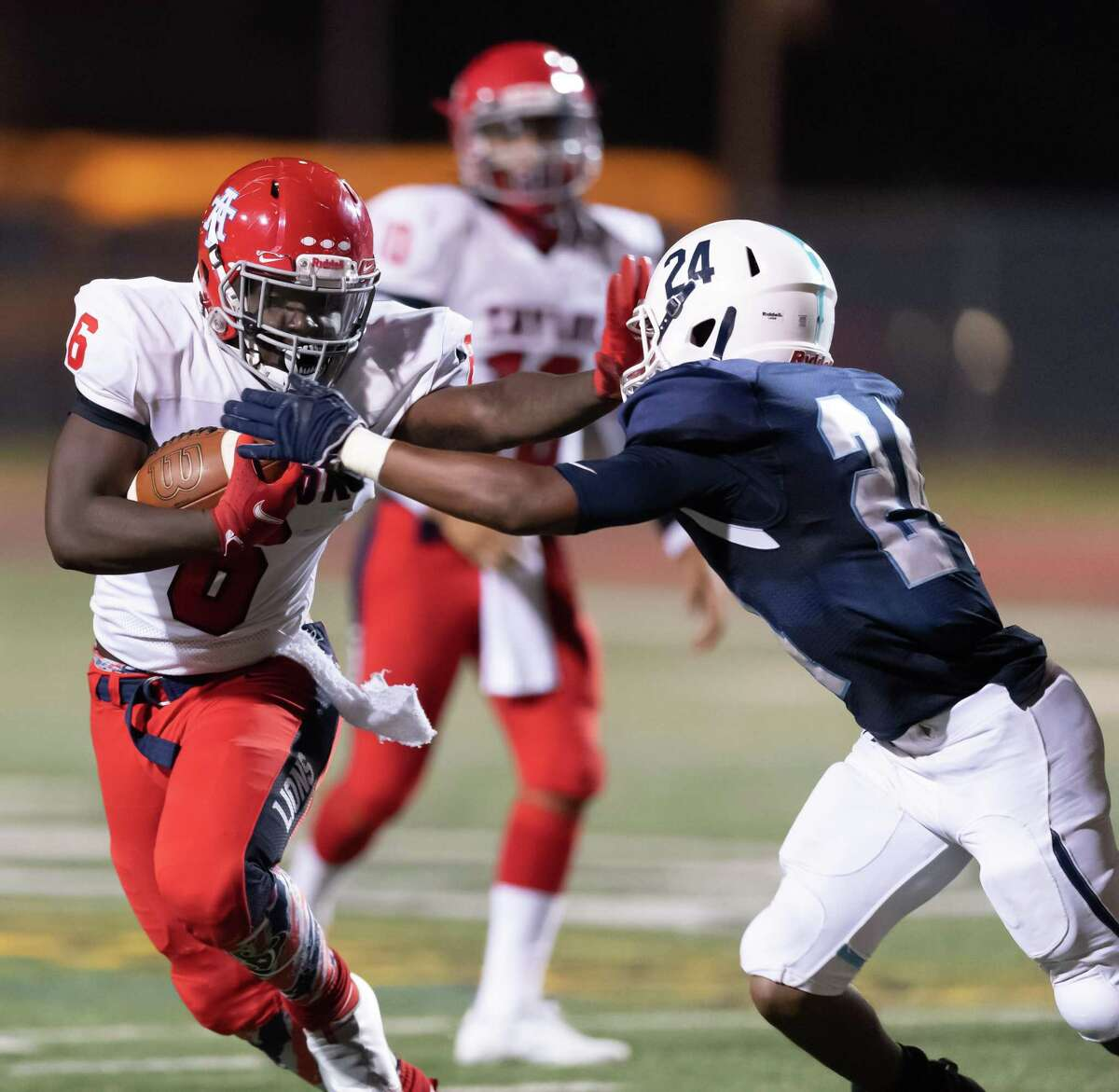 Alonzo Hines (6) of the Alief Taylor Lions stiff arms Kyle Brown (24) of the Alief Elsik Rams in the first half during a High School football game on Friday, October 16, 2020 at Crump Stadium in Houston Texas.