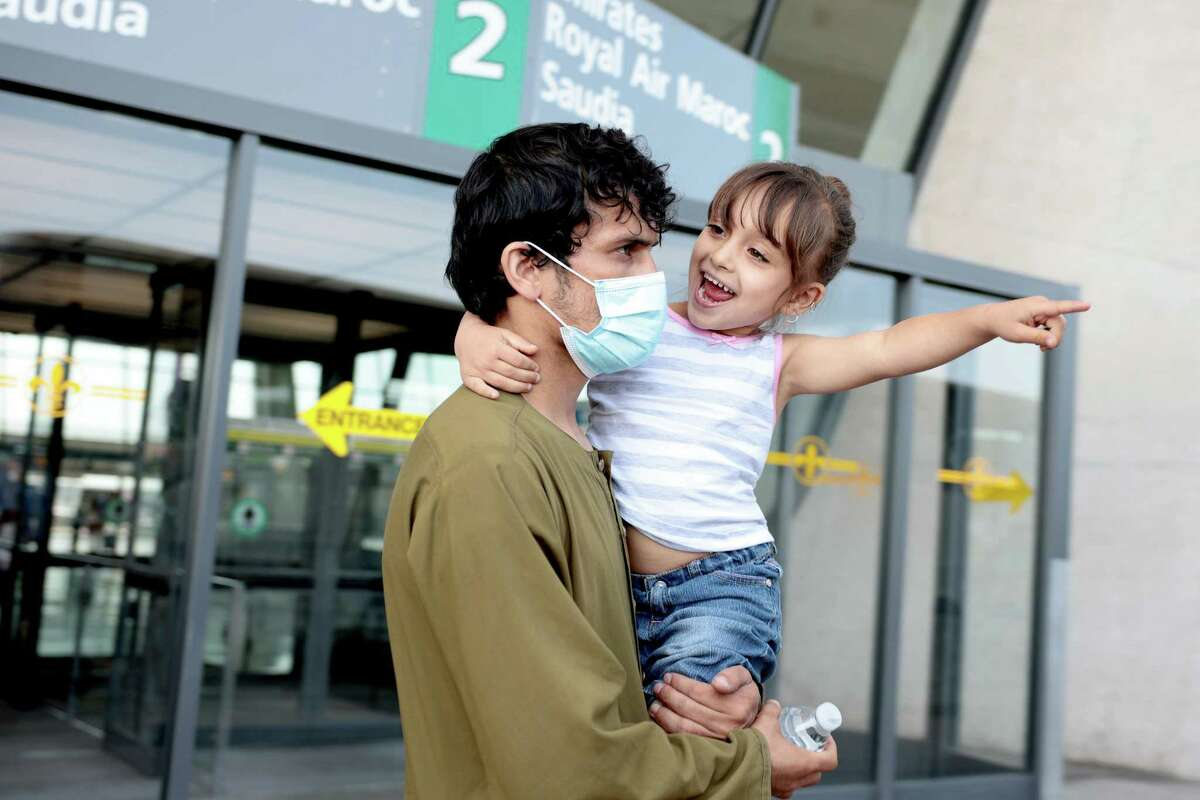 DULLES, VIRGINIA - AUGUST 25: A young girl points to a bus that will take people evacuated from Kabul Afghanistan to a refugee processing center after arriving to the Dulles International Airport on August 25, 2021 in Dulles, Virginia. According to the U.S. Department of Defense, five evacuation flights from Kabul, Afghanistan have landed at the Dulles Airport carrying 1,200 Afghan refugees in last day. The White House also announced that since August 14, the U.S. has evacuated and facilitated the evacuation of approximately 82,300 people on US military and coalition flights. (Photo by Anna Moneymaker/Getty Images) *** BESTPIX ***