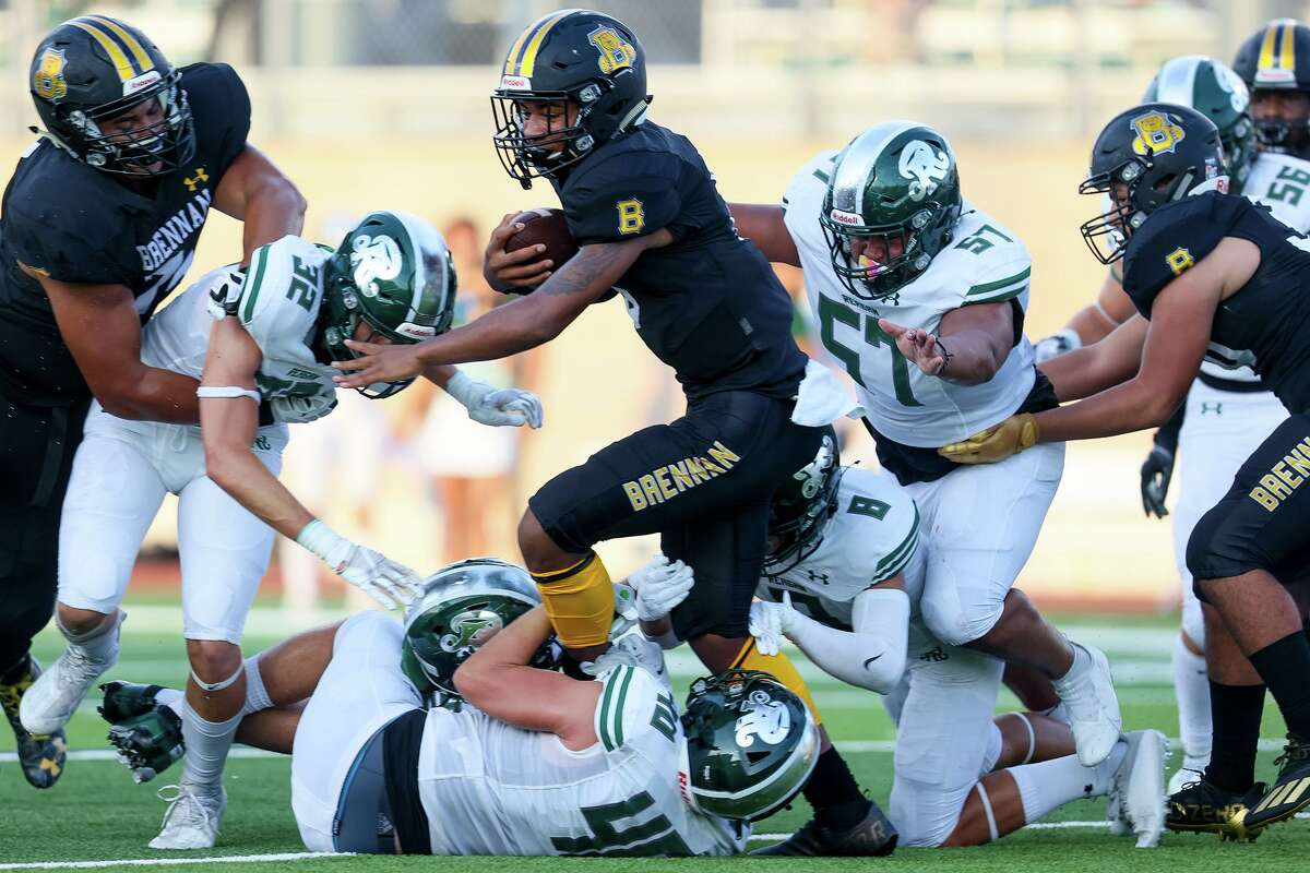 Brennan quarterback Ashton Dubose, center, is stopped by the Reagan defense during the first half of their high school football game at Farris Stadium on Friday, Aug. 27, 2021.