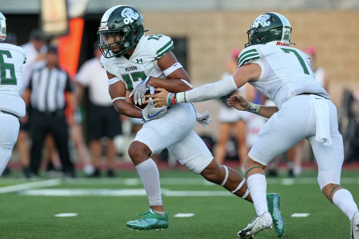 Reagan's Carson Green takes a handoff from Britton Moore during the first half of their high school football game with Brennan at Farris Stadium on Friday, Aug. 27, 2021.