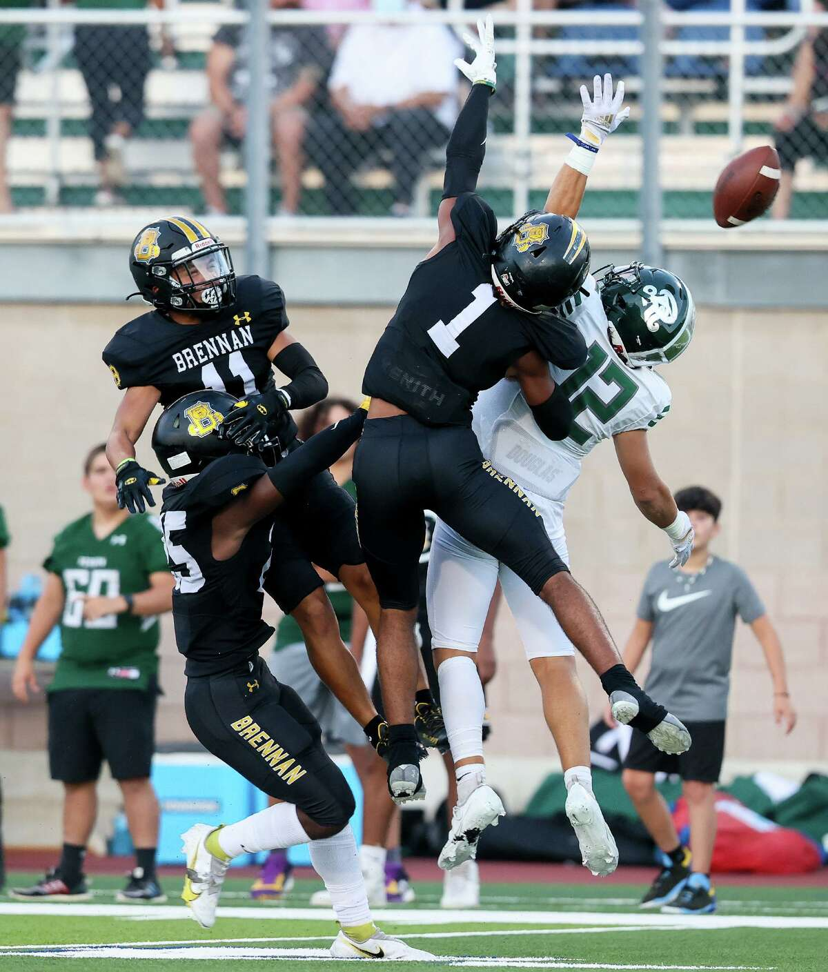 Brennan's Malik Tolbert, from left, Gavin Ramos and Tyler Turner defend a pass intended for Reagan's Lance Lorenz during the first half of their high school football game at Farris Stadium on Friday, Aug. 27, 2021.