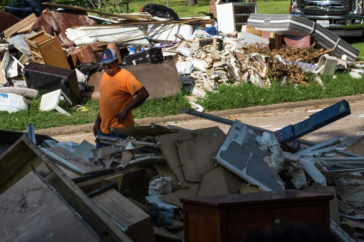 Gregorio Mendoza walks past a debris pile in the Arbor Oaks neighborhood on Wednesday, Sept. 20, 2017, in Houston. The neighborhood used to be home to 160 houses and is now down to 13, after most of the homeowners, having flooded repeatedly, sold to the county Flood Control District.