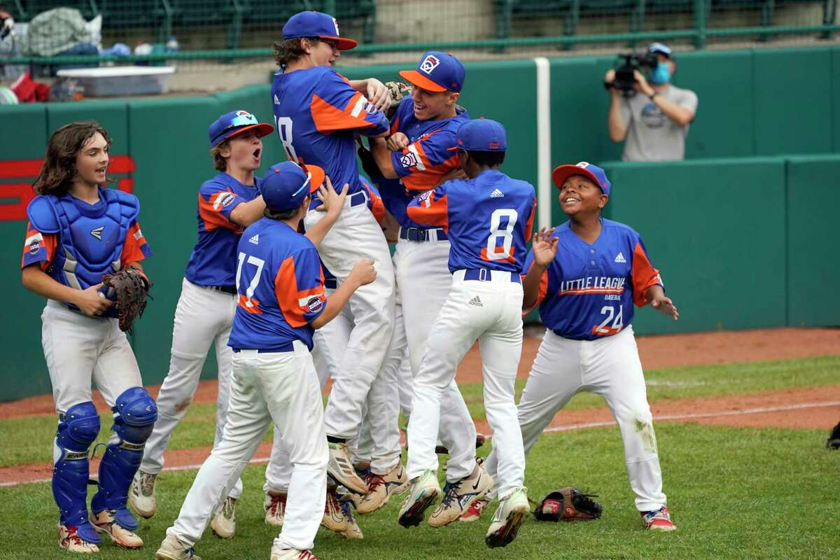 FILE - Taylor, Mich.'s Jakob Furkas (18) and Cameron Thorning, center, celebrate with teammates after a win over Honolulu, Hawaii, in a baseball game at the Little League World Series tournament in South Williamsport, Pa., Saturday, Aug. 28, 2021.