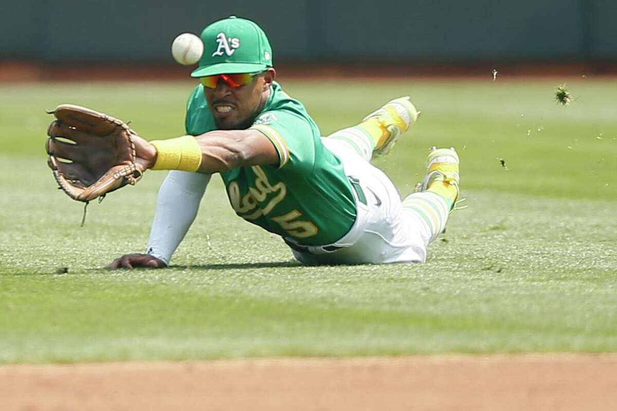 Oakland Athletics second baseman Tony Kemp (5) makes the diving catch in the second inning during an MLB game against the New York Yankees at RingCentral Coliseum on Saturday, Aug. 28, 2021, in Oakland, Calif.