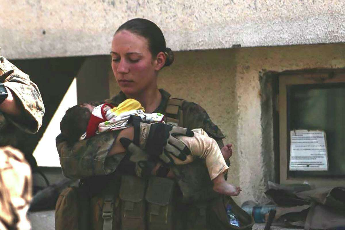 Marine Sgt. Nicole Gee holds a baby at the Kabul airport days before her death in a suicide blast.