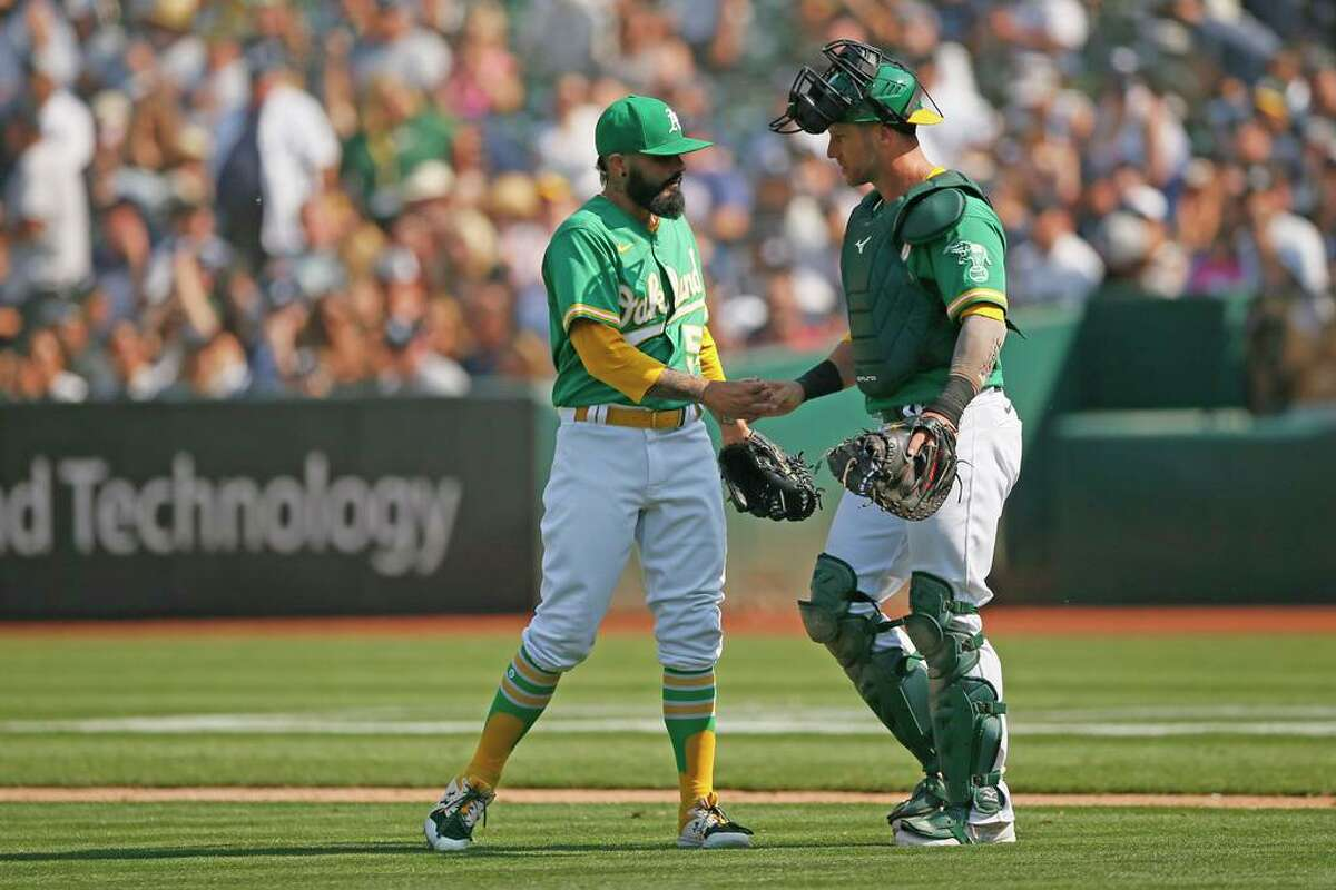 Oakland Athletics Sergio Romo (54) and Athletics catcher Yan Gomes (23) congratulate each other after the end of the MLB game against the New York Yankees at RingCentral Coliseum on Saturday, Aug. 28, 2021, in Oakland, Calif. The A's won 3-2.