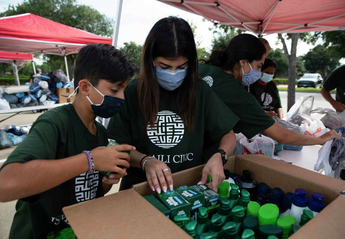 Volunteers Dean Ramzi, 10, left, and Komal Premjee sorting together a box of hygiene products during a supply drive for Afghan refugees and survivors of the earthquake in Haiti at the Ismaili Jamatkhana and Center Saturday, Aug. 28, 2021, in Sugar Land.