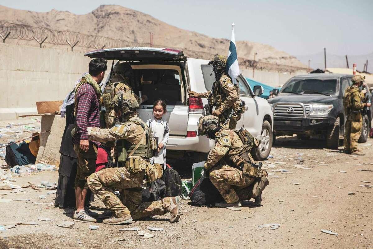 En esta imagen, distribuida por los Marines de Estados Unidos, soldados finlandeses de la coalición asisten a evacuados en controles en el aeropuerto internacional Hamid Karzai de Kabul, Afganistán, el 24 de agosto de 2021.