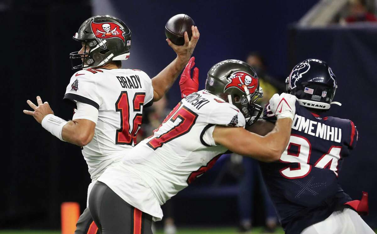 Tampa Bay Buccaneers quarterback Tom Brady (12) gets off a pass as tight end Rob Gronkowski (87) blocks Houston Texans defensive end Charles Omenihu (94) during the first half of an NFL football game Saturday, Aug. 28, 2021, in Houston.
