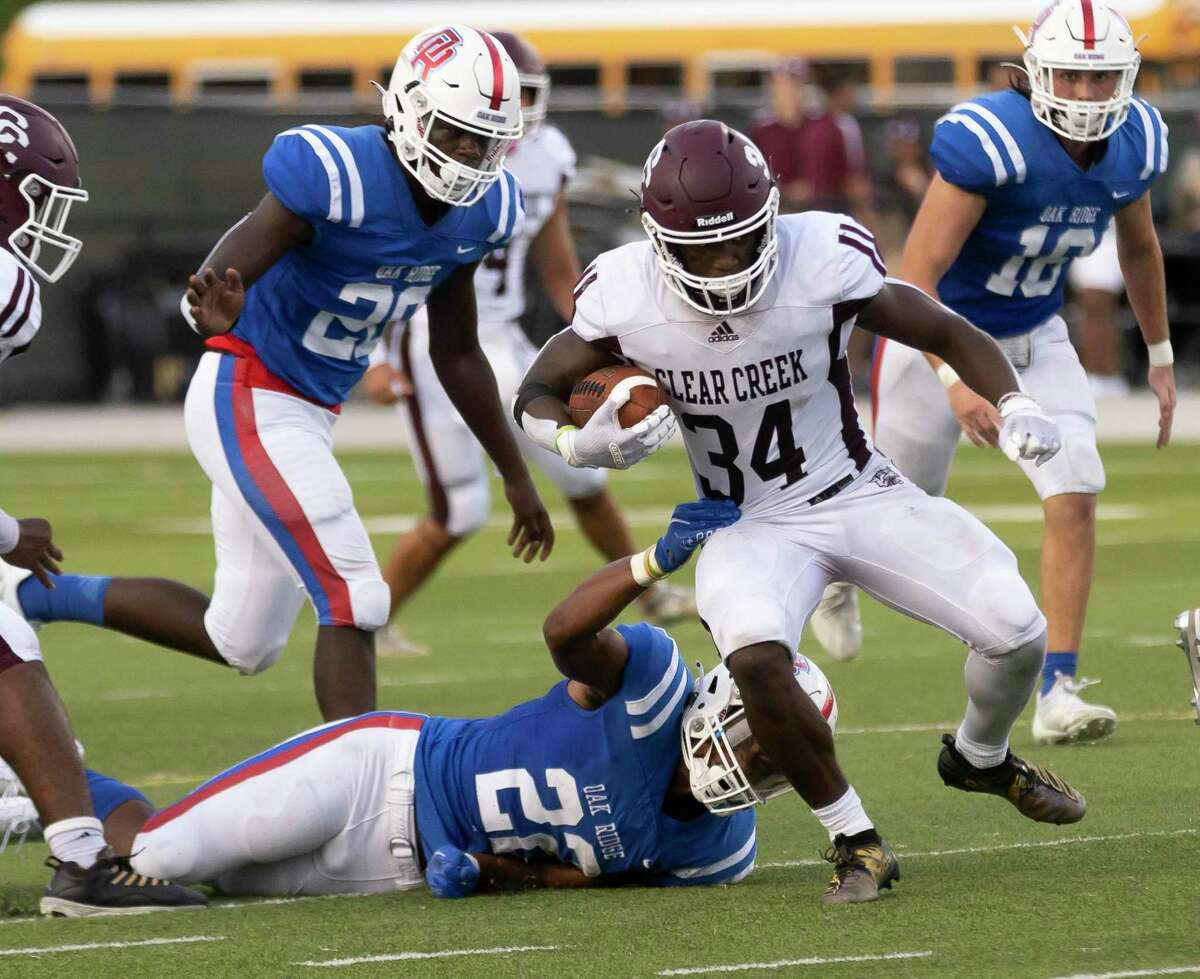 Oak Ridge defensive back Jordan Holmes (22) grabs onto Clear Creek running back Rocky Ketchum (34) during the second quarter of a non-district football game at Woodforest Bank Stadium, Saturday, Aug. 28, 2021 in Shenandoah, Texas.