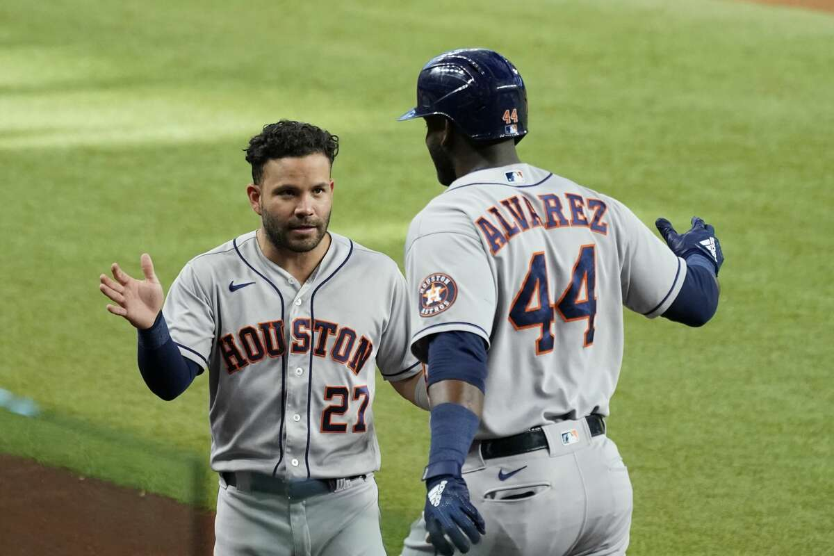 Houston Astros' Jose Altuve (27) and Yordan Alvarez (44) celebrate a solo home run by Alvarez in the second inning of a baseball game against the Texas Rangers in Arlington, Texas, Saturday, Aug. 28, 2021. (AP Photo/Tony Gutierrez)