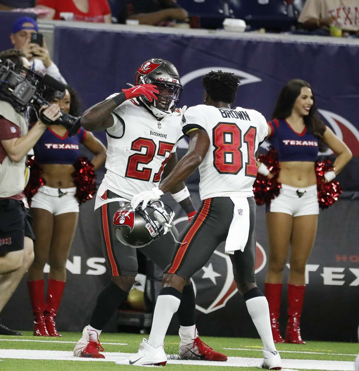 Tampa Bay Buccaneers running back Ronald Jones II (27) and wide receiver Antonio Brown (81) celebrate a touchdown during the first half of an NFL pre-season football game at NRG Stadium, Saturday, August 28, 2021, in Houston.
