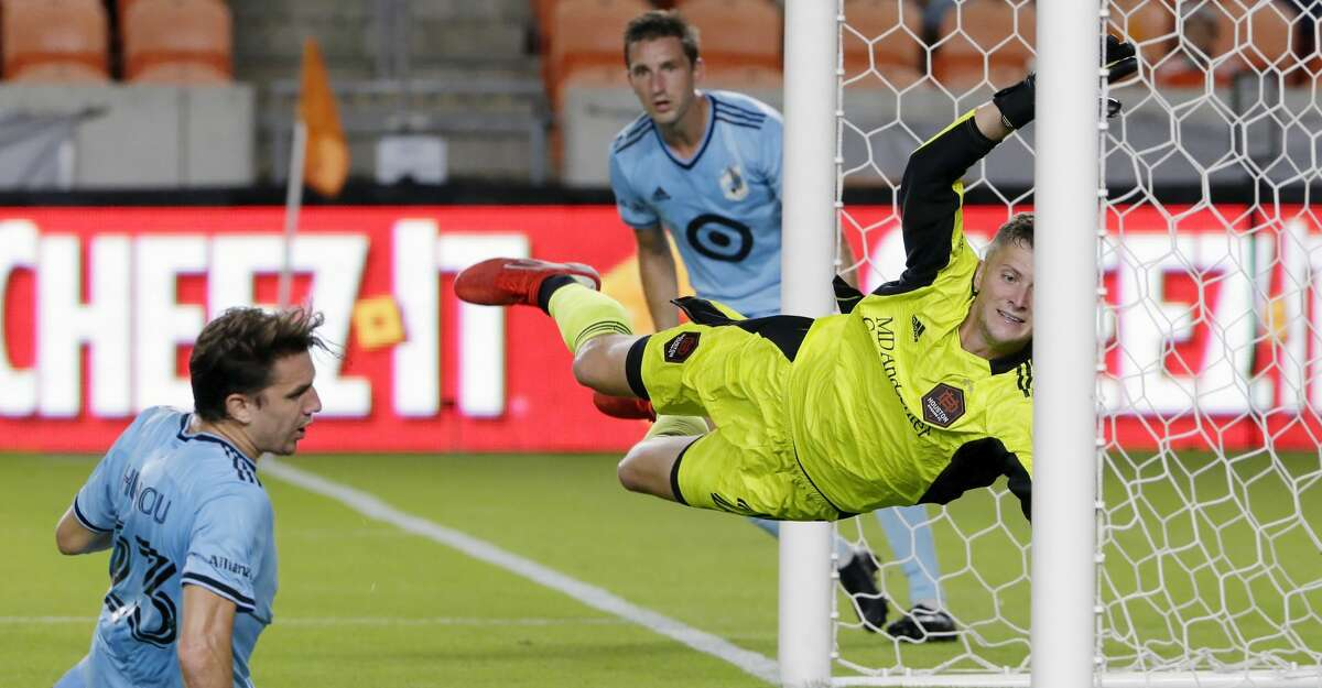 Minnesota United midfielder Adrien Hunou, left, slides in after kicking a goal past Houston Dynamo goalkeeper Michael Nelson, right, who dives during the first half of an MLS soccer match Saturday, Aug. 28, 2021, in Houston. (AP Photo/Michael Wyke)