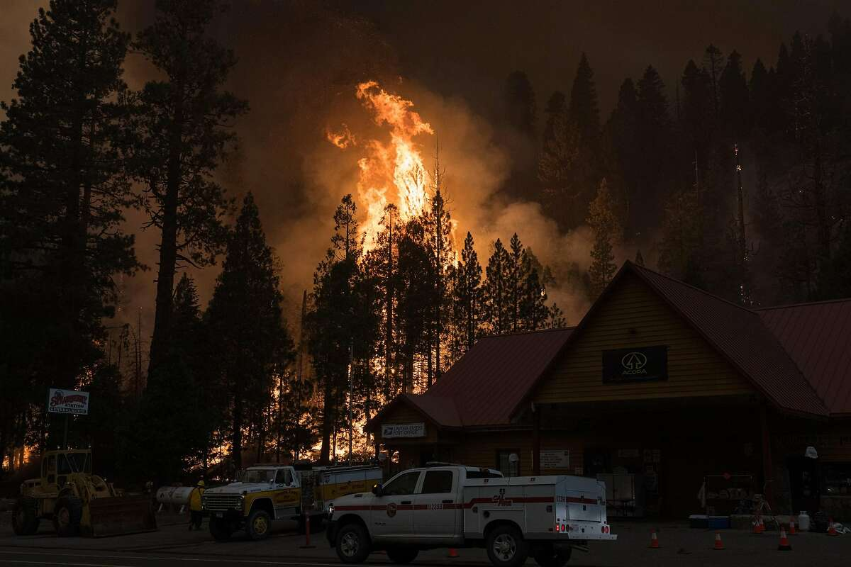 A controlled backfire burns behind the Strawberry Station General Store in El Dorado County during the Caldor Fire.