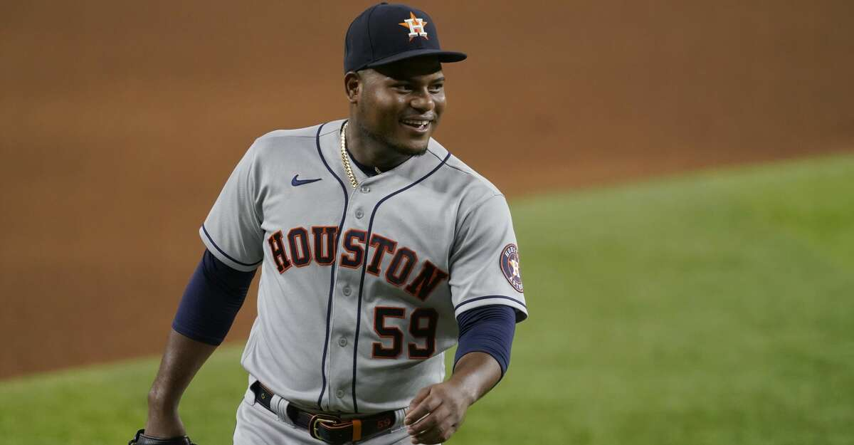 Houston Astros starting pitcher Framber Valdez looks at catcher Martin Maldonado standing nearby after working in the seventh inning of a baseball game against the Texas Rangers in Arlington, Texas, Saturday, Aug. 28, 2021. (AP Photo/Tony Gutierrez)
