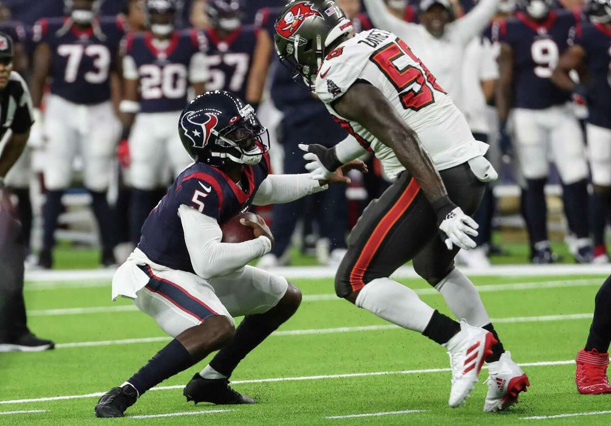 Houston Texans quarterback Tyrod Taylor (5) stumbles in the backfield as he is chased down by Tampa Bay Buccaneers linebacker Shaquil Barrett (58) during the first half of an NFL football game Saturday, Aug. 28, 2021, in Houston.